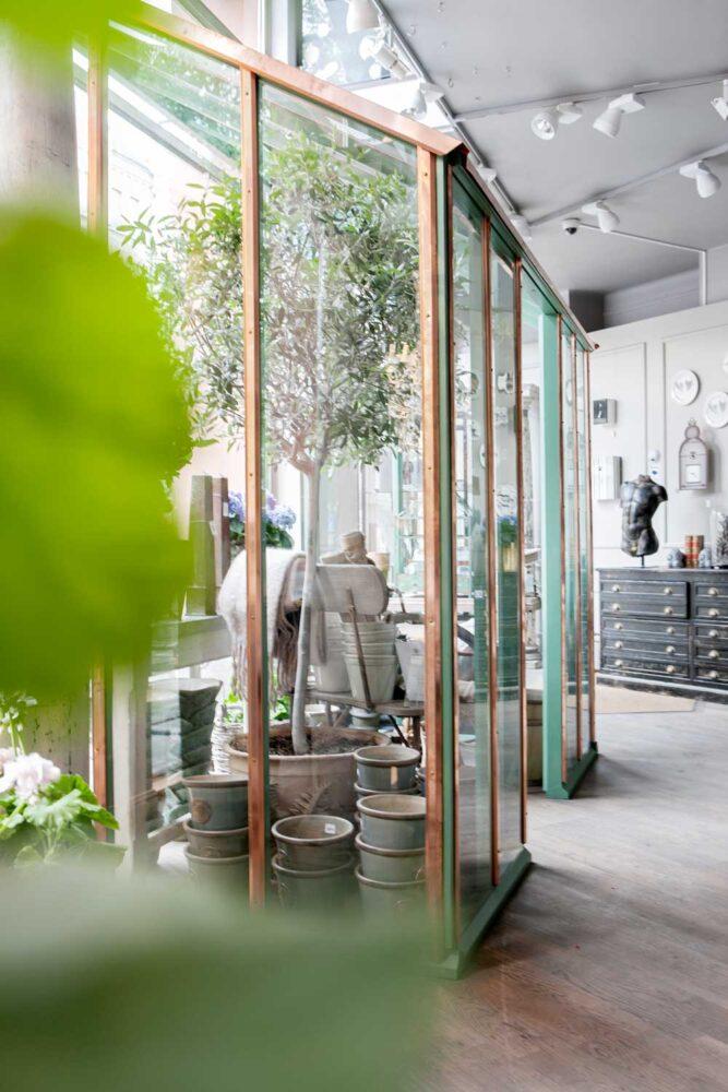 I butiken Oscar & Clothilde finns ett grönt växthus med kopparlister med pulpettak från Sweden Green House