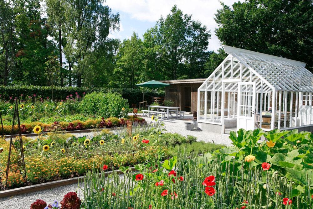 Vitt växthus bland blomsterrabatter.