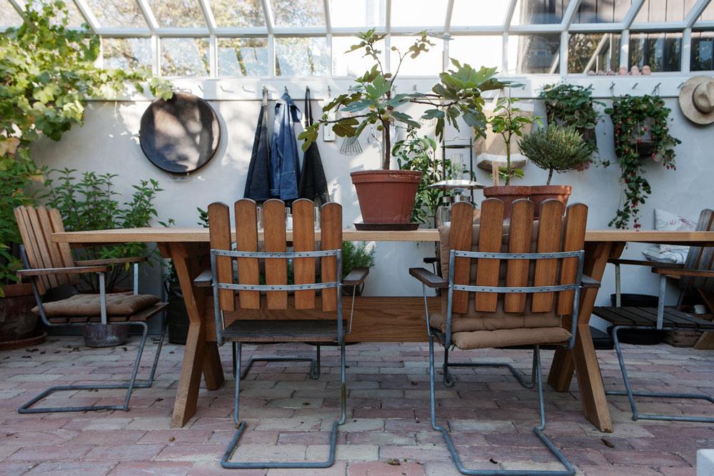 Växthusinteriör med bord, trädgårdsstolar, krukodlingar och en knopphängare för värktyg och förkläden.