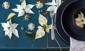Dukningstips i adventstider med vita julstjärnor och rustikt svart keramik