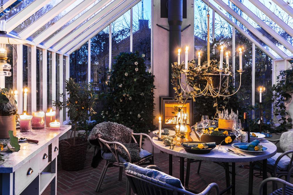 En uppdukat middagsbord i växthuset ogifte av tänd brasa och brinnande stearinljus