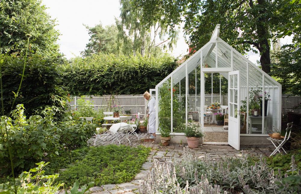 vitmålat växthus sett från sidan, med sadeltak. Eva Halfwordson från Sweden Green House är utanför