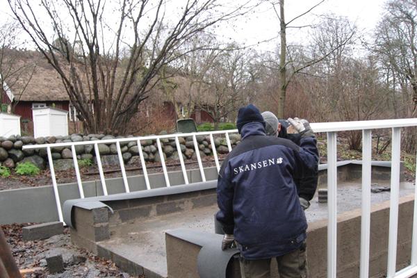 Två män monterar ett växthus