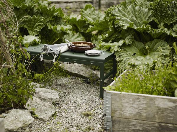 Skageraks bänk med vändbar sits som kan användas som antingen blombord eller sittplats. En grön ärhär placerad i lummig trädgårdsgrönska