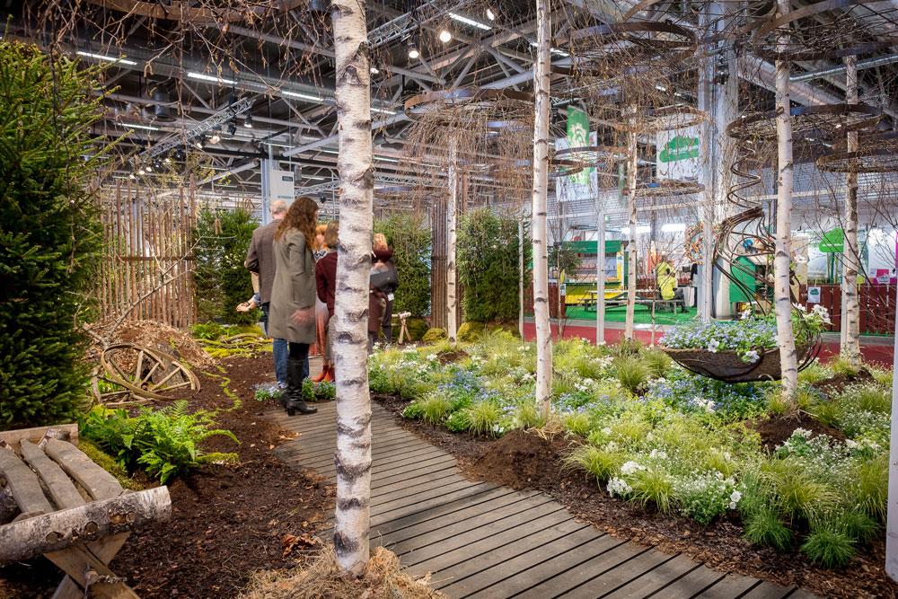 En visningsträdgård med björkstammar och skogskänsla från trädgårdsmässan Nordiska trädgårdar.
