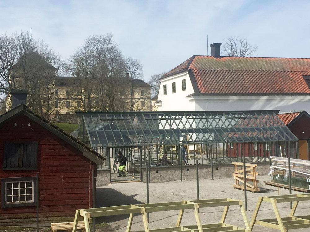 Ett grönmålat växthus under konstrukition på Lövsta slott i Örebrotrakten