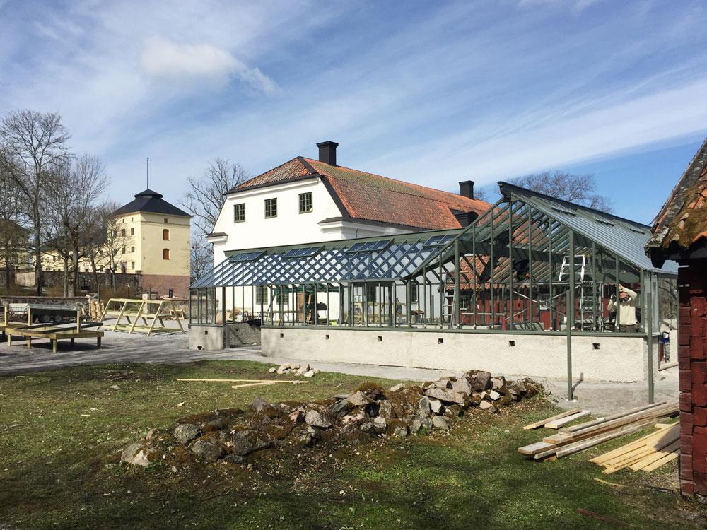 Ett växthus under konstruktion på gården utanför Lövsta slott i örebrotrakten. Det är målat i en djupgrön färg, Lövstagrönt