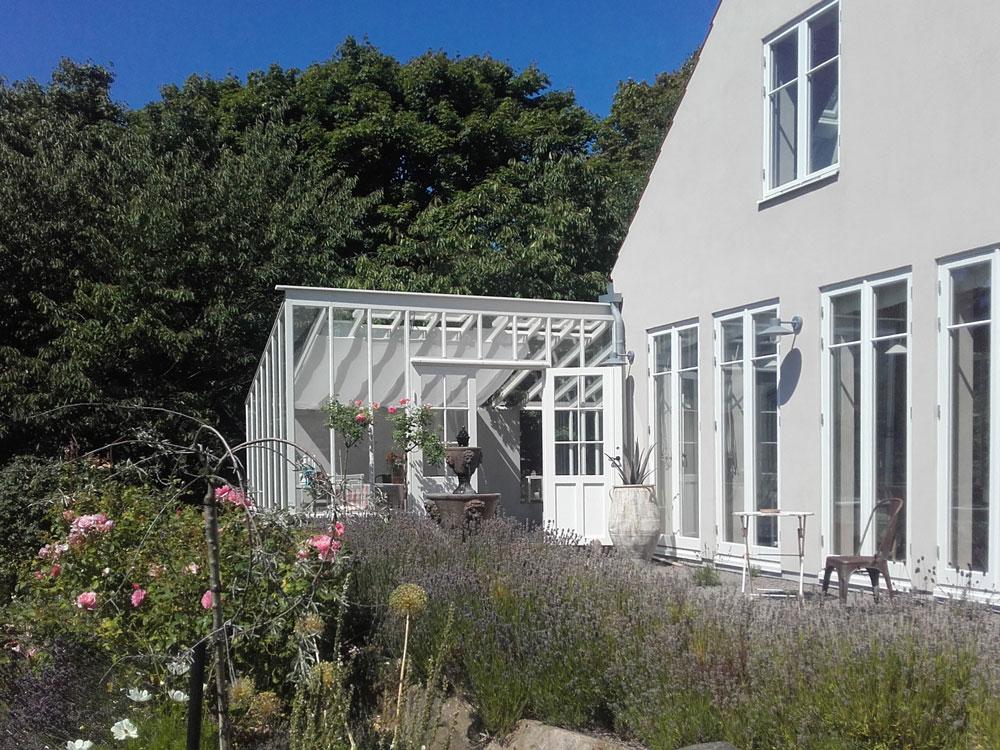 Ett bostadshus med ett tillbyggt växthus i anslutning i vinkel med huskroppen.