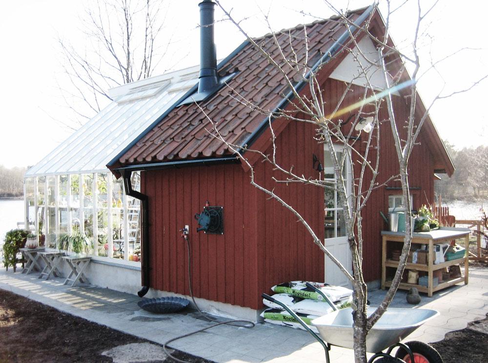Ett växthus som byggts ihop med en röd förrådsbyggnad. Växthuset har vänts mot sjön som ligger intill