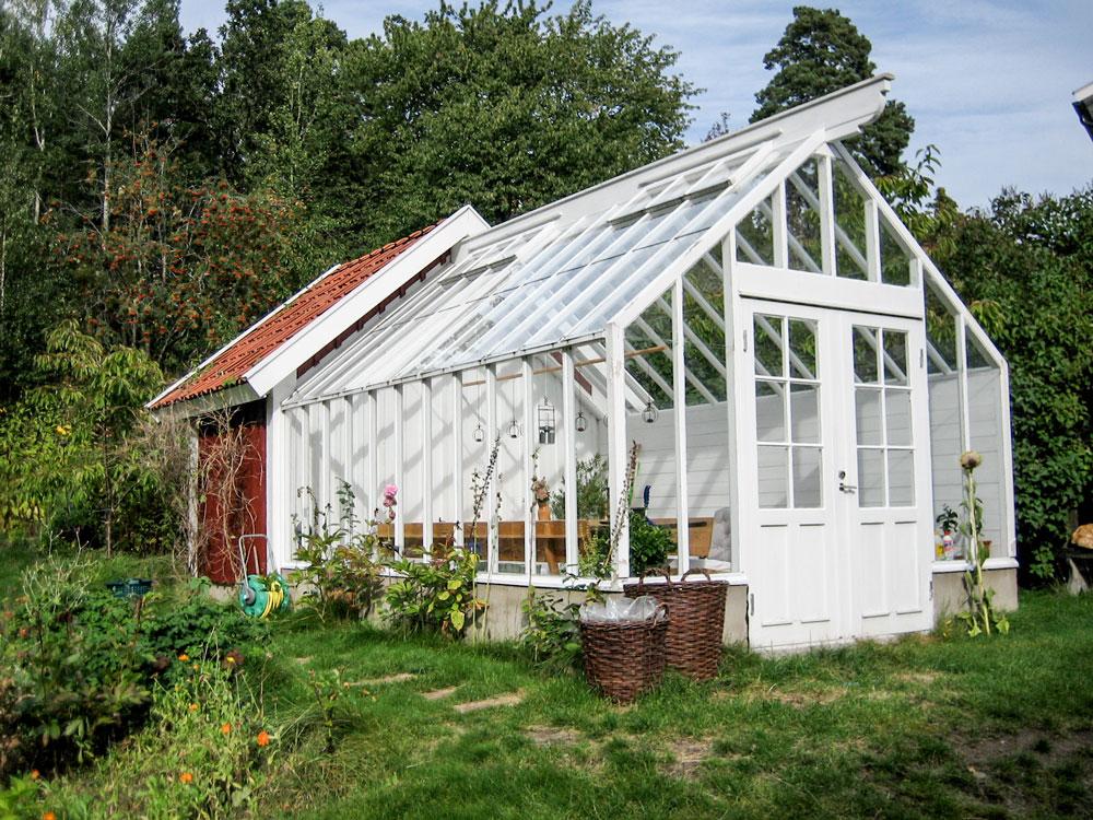 Ett växthus som byggts som förlängning tillsammans med en röd förrådsbyggnad