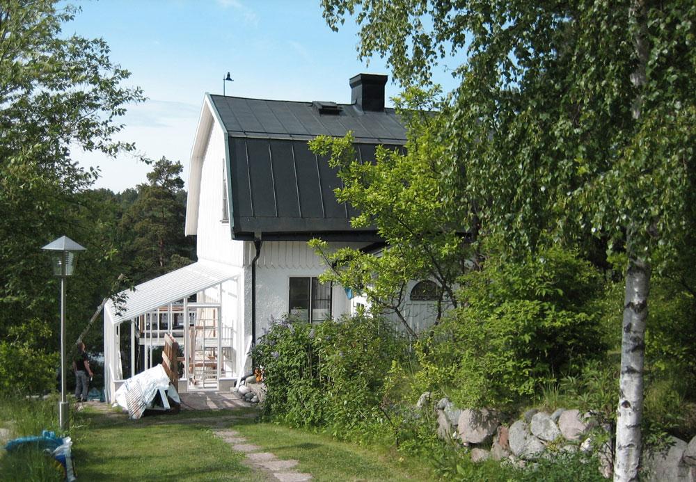 Ett vitt växthus med pulpettak håller på att byggas med på ett vitt bostadshus