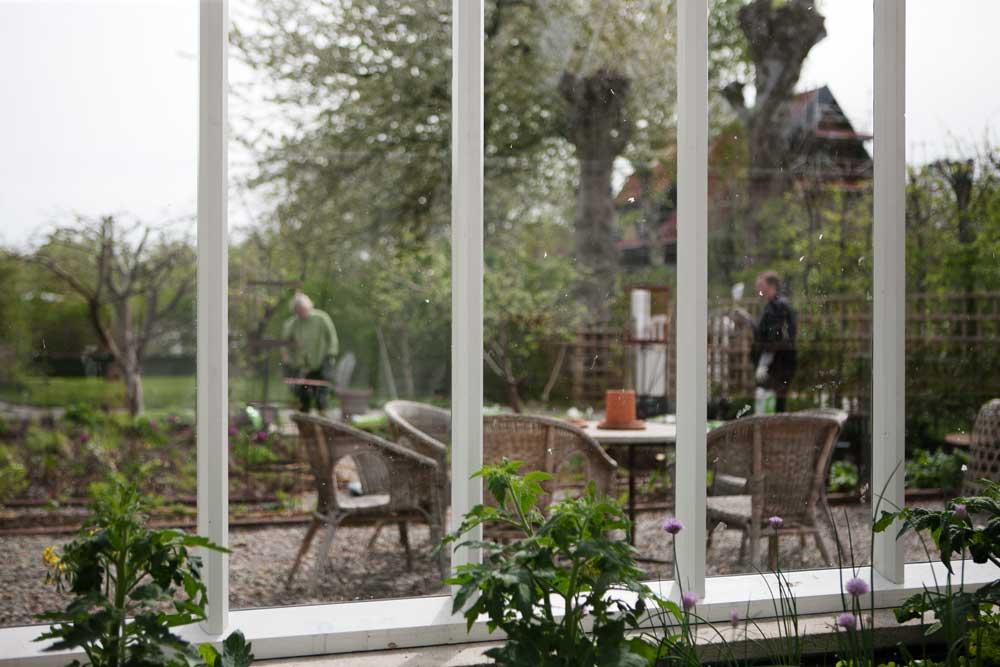 Vy inifrån växthuset ut mot trädgården och odlingsbäddarna utanför