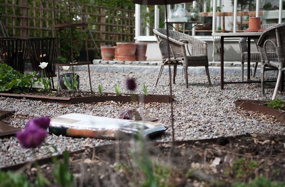 Platsen utanför växthuset med den klassiskt utformade rabatten som avgränsas av snigelskyddad kortenstål