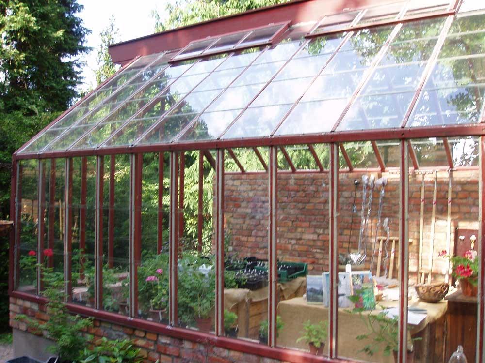 Ett av de växthus som vi byggt är målad i en djup röd färg som matchar tegelgrunden fint.