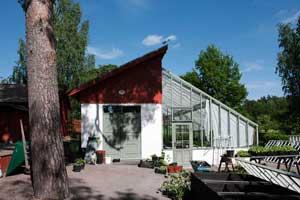 Det grönmålade växthuset från gaveln så att man ser hur det sammanlänkar med förrådsbyggnaden vid trädgårdsmästeriet på Stabergs bergmangård.