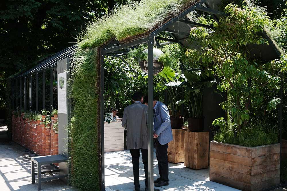 Två besökare som diskuterar i en visningsträdgård producerad av Gally på den franska trädgårdsmässan Jardins jardin