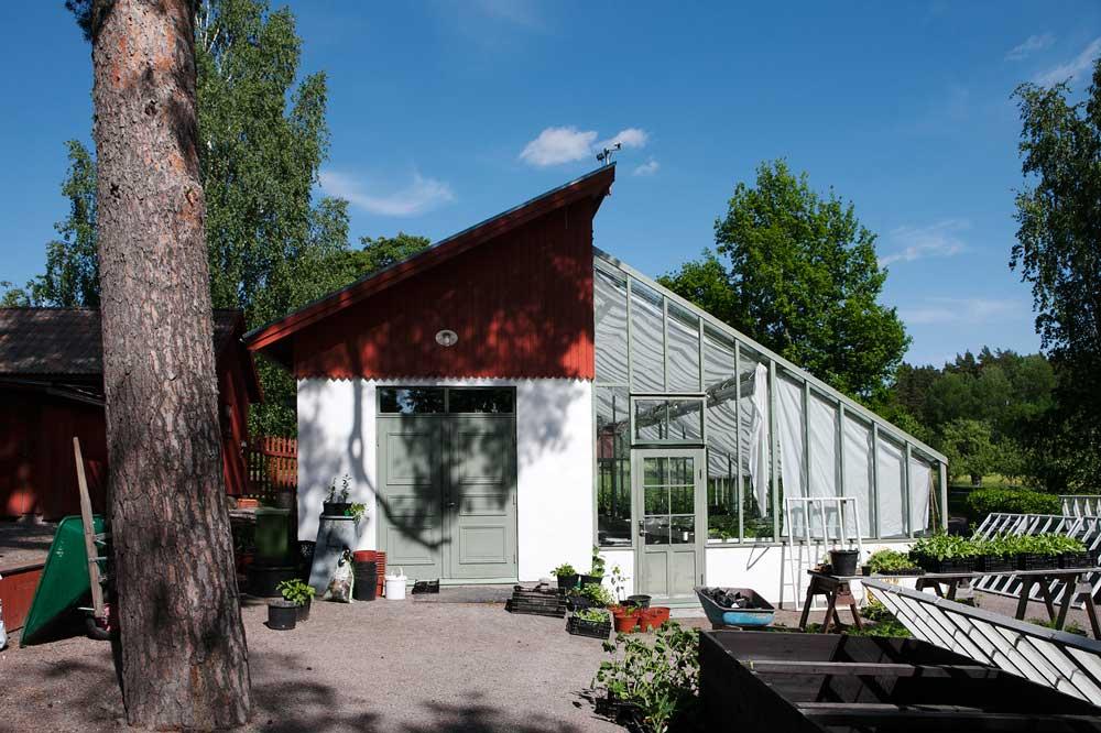 Det grönmålade växthuset från gaveln så att man ser hur det sammanlänkar med förrådsbyggnaden vid trädgårdsmästeriet på Stabergs bergmansgård.