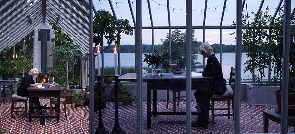 Victoria Skoglund sitter i sitt nybyggda träväxthus och arbetar.