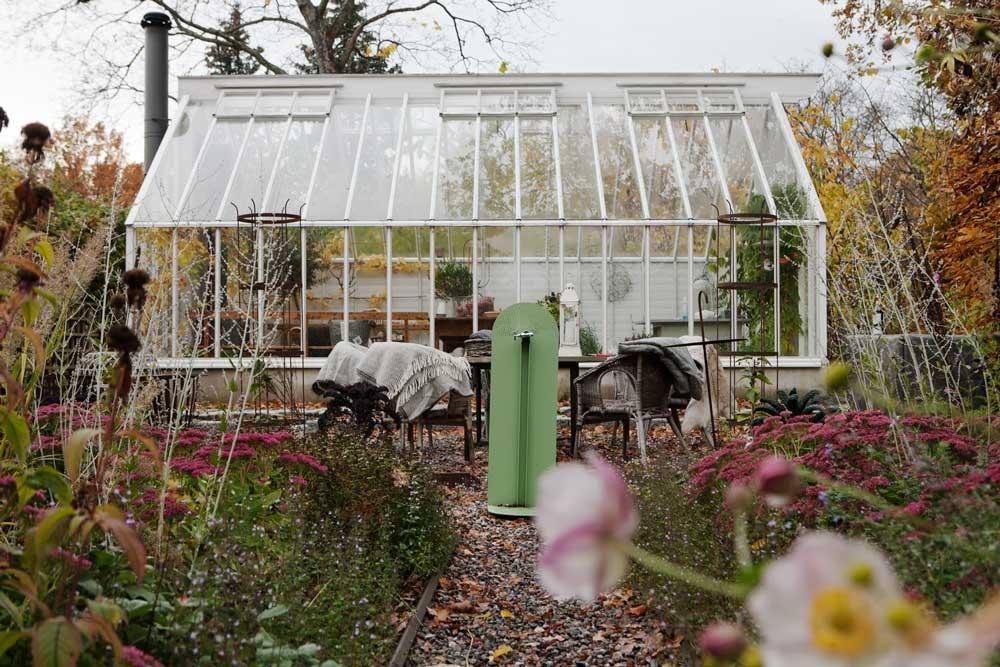 Växthuset i Nacka omgiven av rabatter och träd i höstfärger.