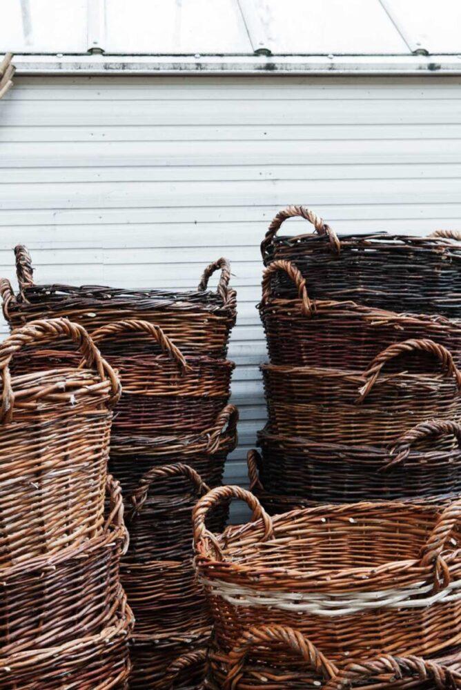 Korgar tillverkade av romer i Rumenien står staplade i varandra utanför växthuset i Nacka.
