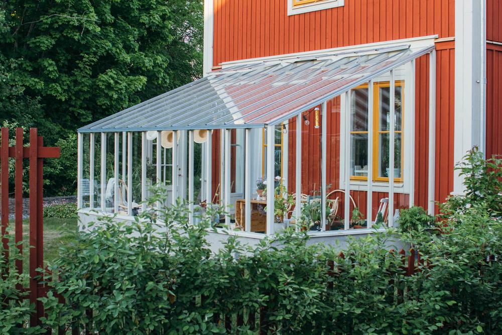 Vitt växthus med pulpettak.