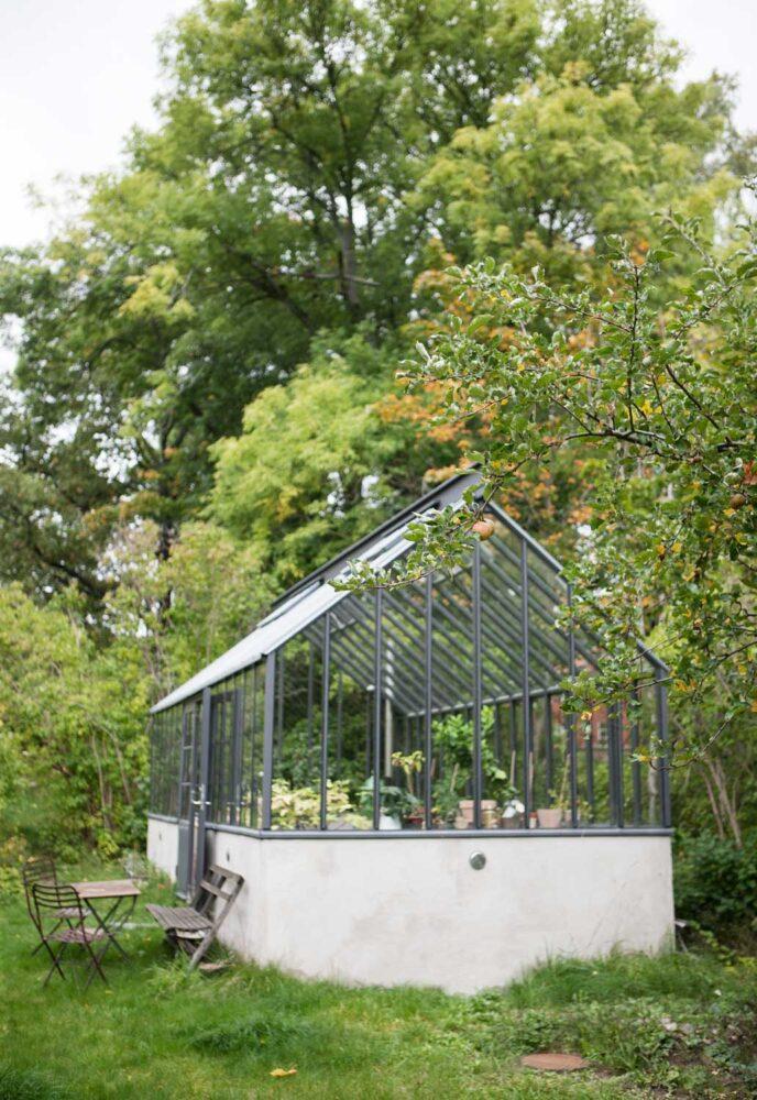 Ett grått växthus i trädgården