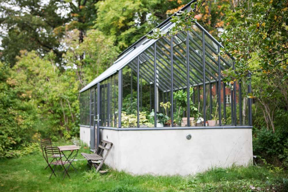 Ett grått växthus med ett bord och stolar utanför