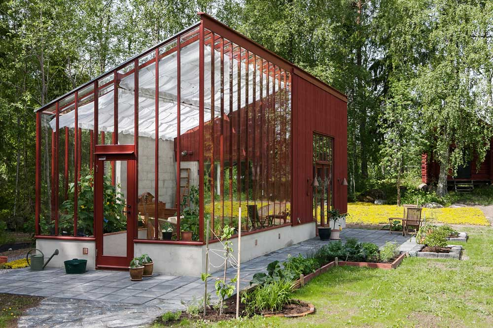 Ett rött pulpetväxthus med enkel helglasdörr.