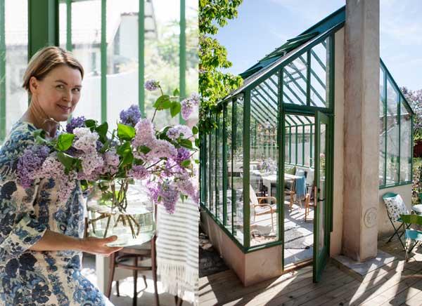 Linda Wahlström är på väg in i det gröna växthuset med en vas fylld av syrener.