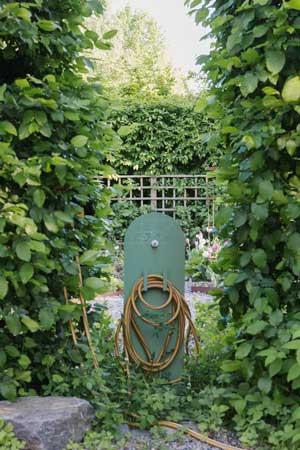 den franska vattenposten i metall håller ordning på trädgårdsslangen.
