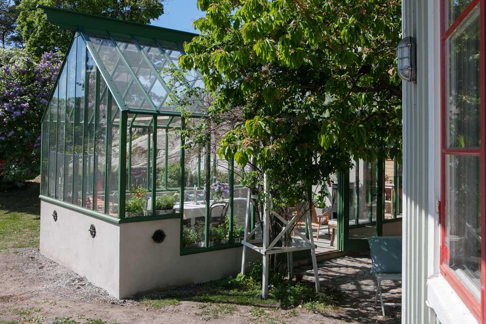 Ett växthus som är byggt med en grund i trappsteg för att få maximalt med ljus trots att man behövde en hög grund för syna syften.