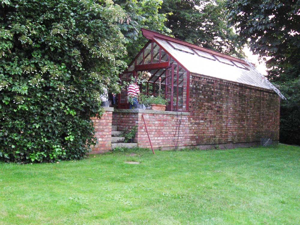 Ett rött växthus som är byggt mot en mur av tegel.