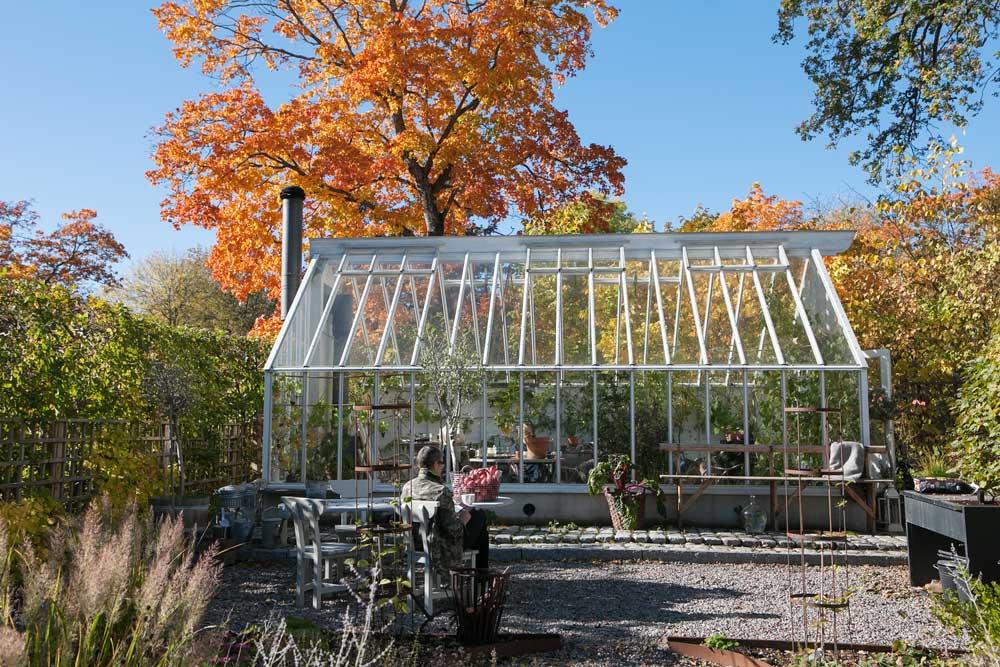 Växthuset i Nacka i oktoberomgiven av vackra träd i höstfärger.