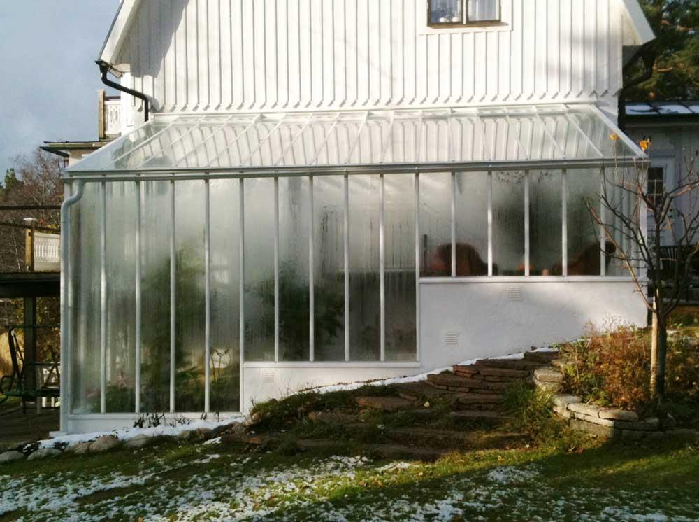 Ett växthus med pulpettak mot vägg.