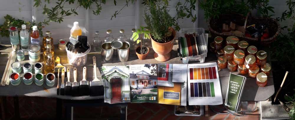 Linolja och linoljefärg uppdukat på ett bockbord tillsmmans med information och tidningar.
