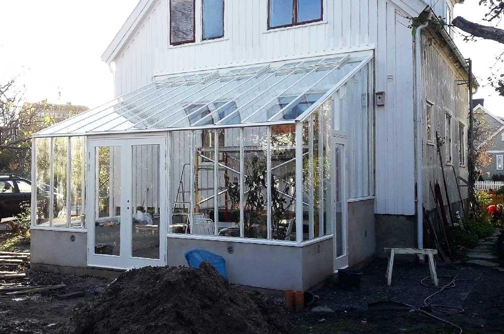ett växthus mot vägg med två ingångar