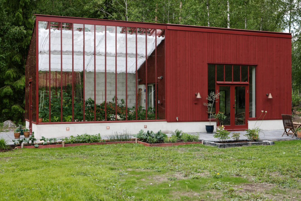 Arkitektritat falurött växthus mot en atelje