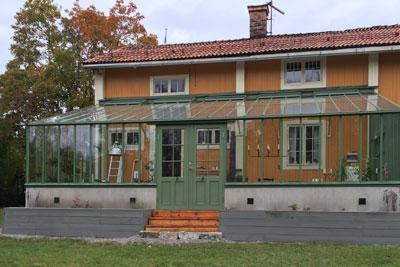 Grönt växthus mot gult hus
