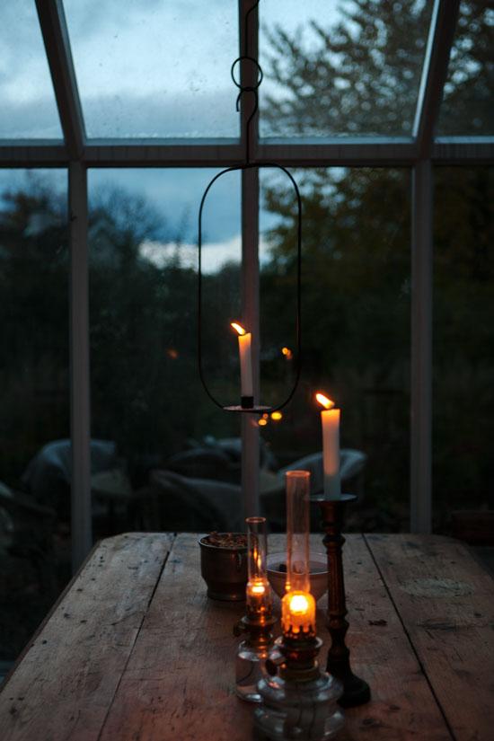 Tända ljus på ett gammalt träbord i växthuset.