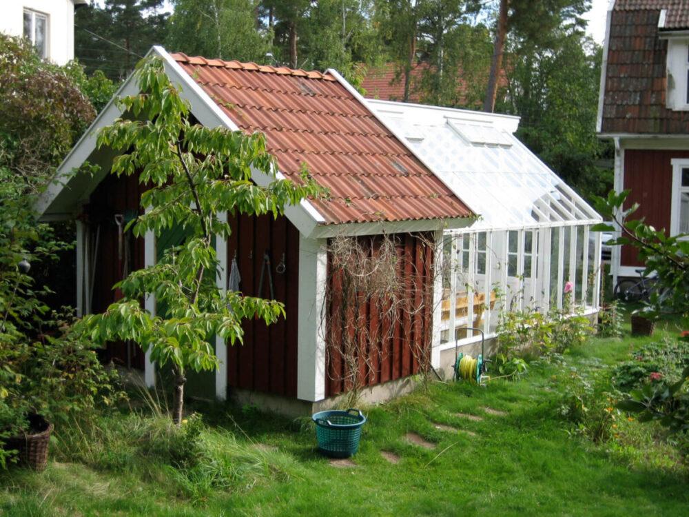 Vitt växthus mot förråd.