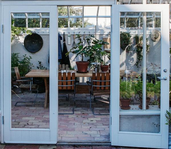 En helglasdörr till ett vitt växthus
