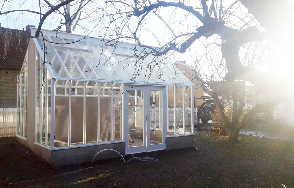 Ett växthus med sadeltak som precis är färdigbyggt i en trädgård i Skarpnäck.