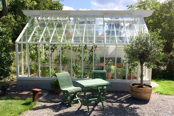 Växthus och en grön utemöbel