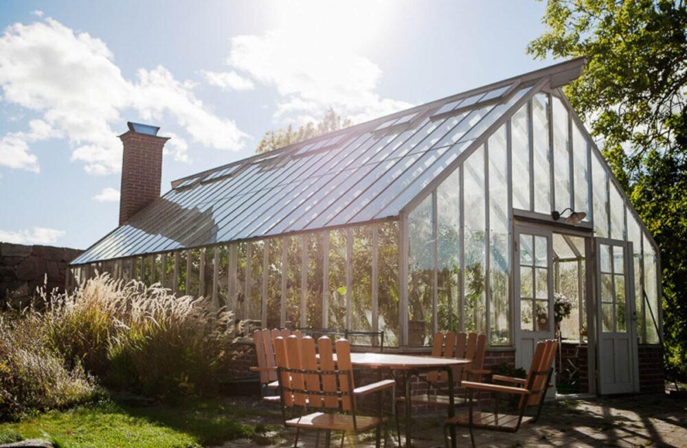 Ett bord med stolar framför ett stort växthus