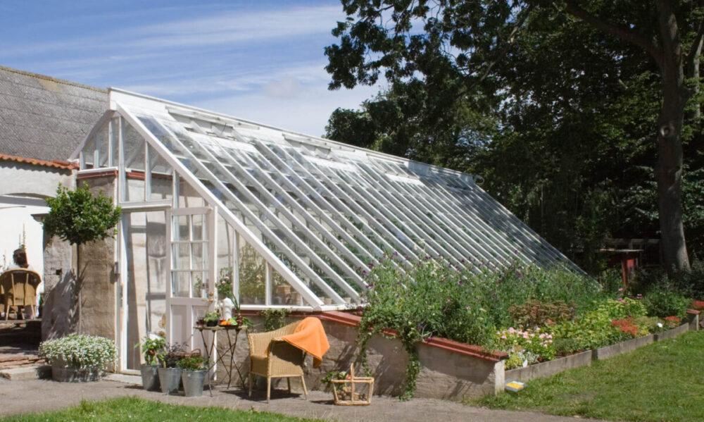 Arkitektritat växthus med brutet tak.