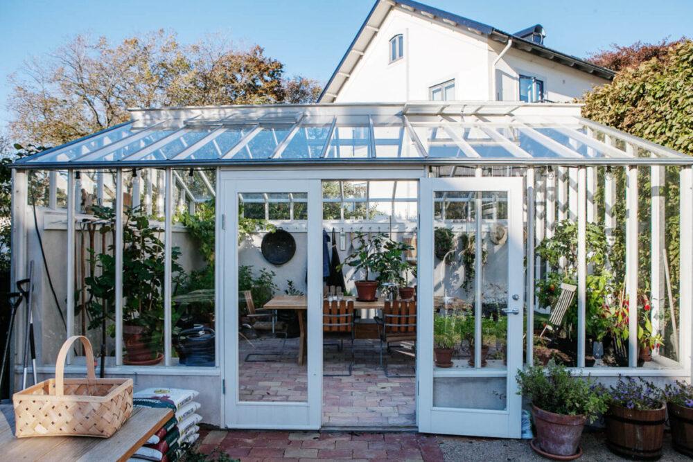 Ett vitt växthus med helglasdörrar