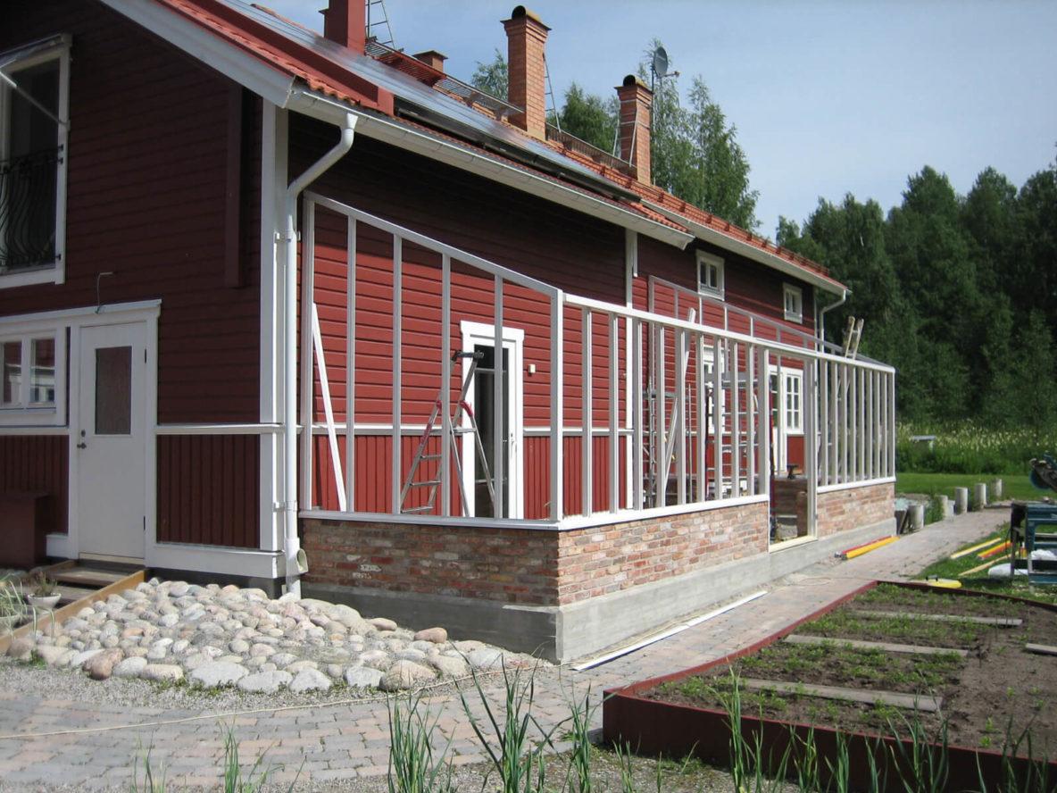 Bygge av vitt växthus mot hus