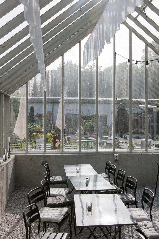 Ett växthus inifrån med bord och stolar