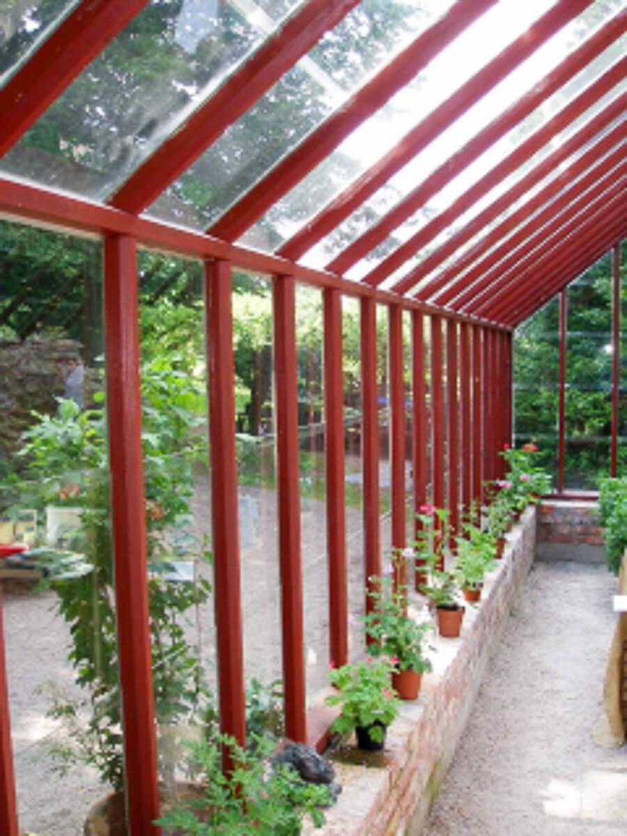 Långsidan på ett tegelstens rött växthus