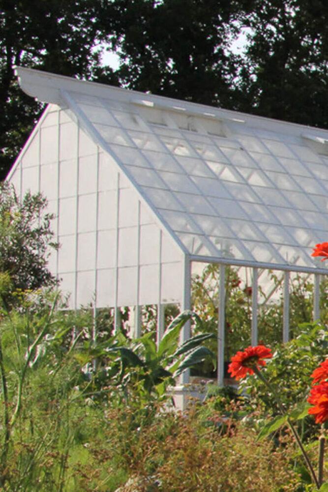 Ett vitt växthus med ett öppna fönster